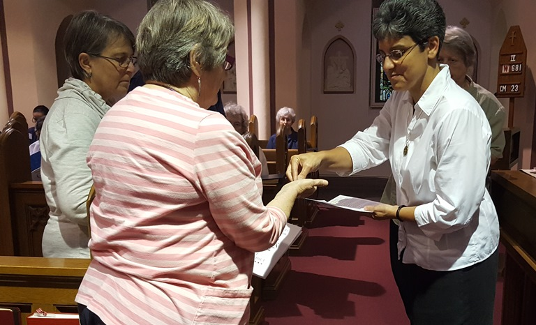 Oblate Novice receives a Benedictine Medal from the Prioress