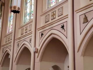 Painted symbols above the arches of the side aisles