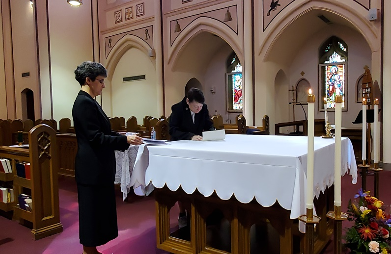 Sister Eileen signs her Renewal of Monastic Profession on the altar