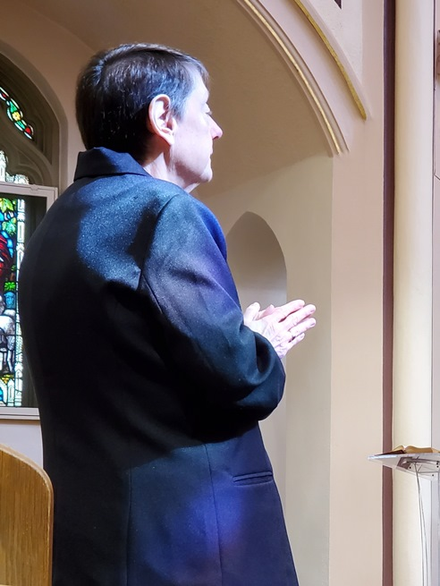 Light from the stained glass windows falls on Sr. Eileen during her Renewal of Monastic Profession