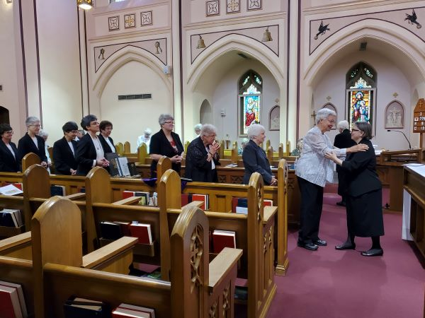 The community  greets the newly-installed Prioress.