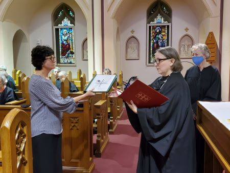 Margaret is presented with a copy of the Constitution of the Federation of St. Scholastica.