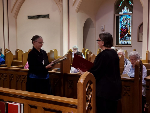Sister Elisabeth presents Sister Edith wiht a copy of the Community Philosophy and a copy of the Constitution of the Federation of St. Scholastica.