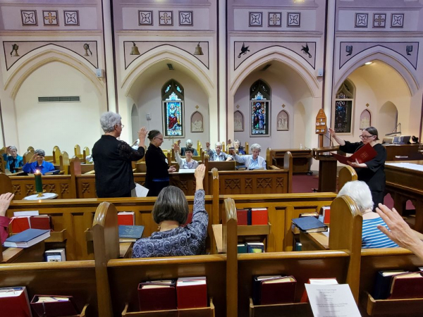 Sister Elisabeth offers a blessing as community members join in the gesture through the raising of hands.