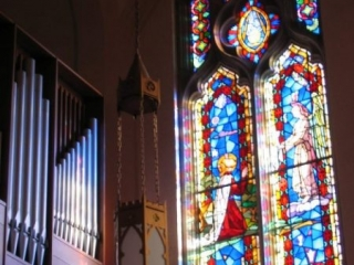 Sunlight shining through the clerestory windows makes a tapestry of color cascade across the organ pipes