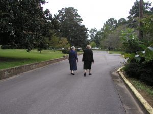 Sisters Kathleen and Eleanor walking the road in front of the monastery after Sunday Mass