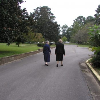 Sisters Kathleen and Eleanor walking the road in front of the monastery