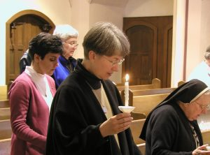 Sisters sing opening hymn with lighted candles
